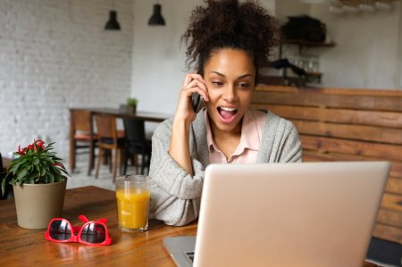 Portrait of a happy young woman using laptop and calling with mobile phone