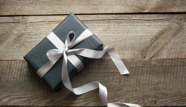 Gift box wrapped in black paper with silver ribbon on wooden surface
