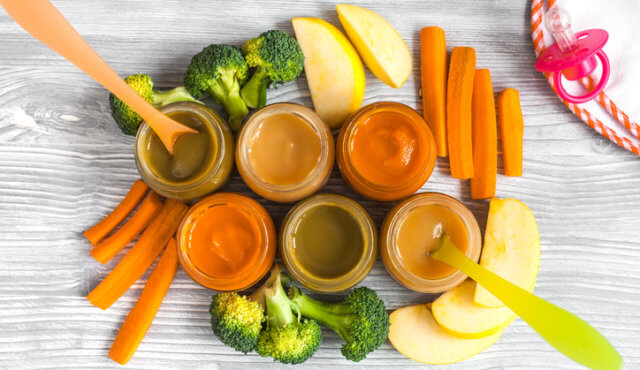 baby vegetable puree on wooden background top view.