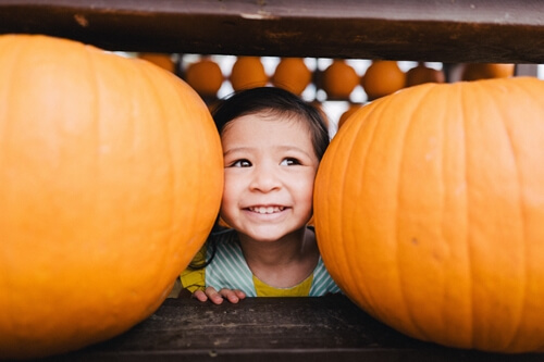 a boy hiding behind some pumpkins