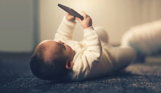 Baby holding smart phone on back
