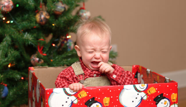 Little boy in gift box crying at Christmas.