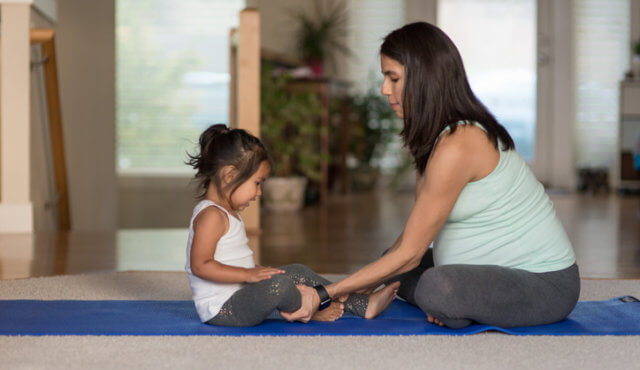A pregnant ethnic mother is doing yoga with her young toddler girl