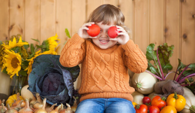 Cute happy little kid with different vegetable harvest, autumn, wood background, countryside, family farm