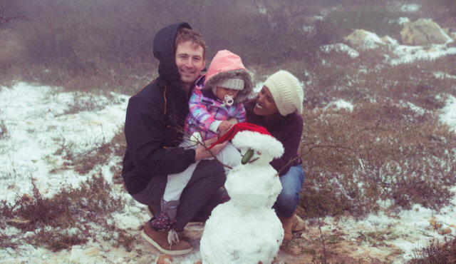 Mixed race happy family sitting with a snowman outdoors.