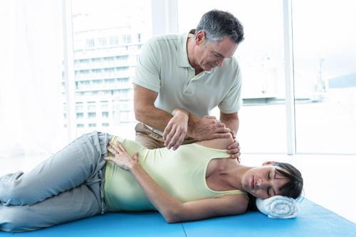 a pregnant woman being worked on by a chiropractor