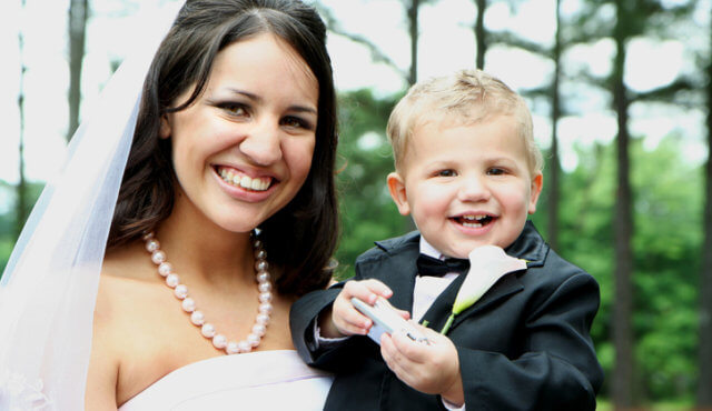 A young bride and her ring bearer smile for the camera.