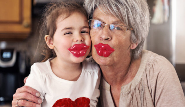 Little girl and grandmother posing with big lips lollypop