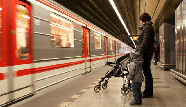 Family looking at train at subway station in Prague
