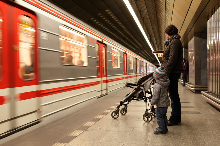 Family looking at train at subway station in Prague