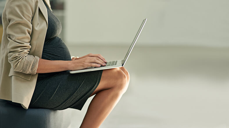 Cropped shot of a pregnant businesswoman using a laptop in an office