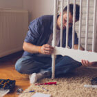A man is sitting on the floor and assembling the baby crib on his own