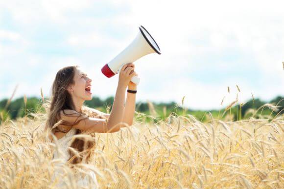 a woman yelling into a megaphone in a farm field