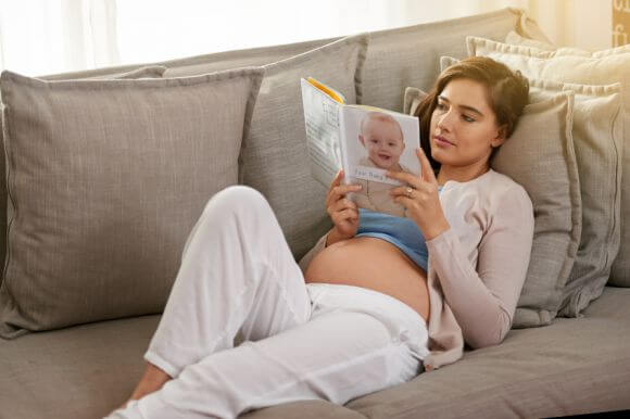 a pregnant woman lying on a sofa reading a baby book