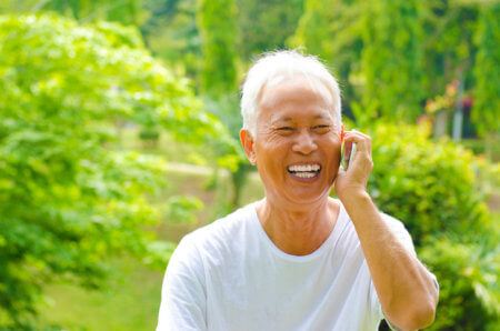 A smiling, elderly man talking on the phone