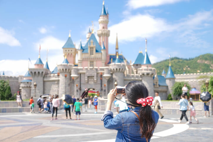 a woman taking a photo at Disneyland