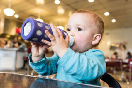 Baby grabbing his baby bottle at a restaurant