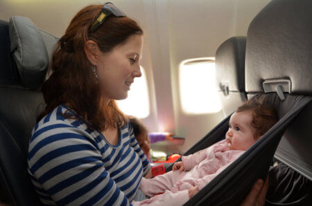 Mother carries her infant baby during flight.Concept photo of air travel with baby.