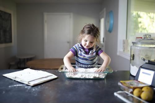 a kid rolling out some dough in the kitchen