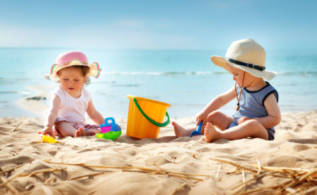 Babygirl and babyboy sitting on the beach in straw hats