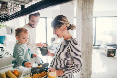 Photo of a young family preparing breakfast together in their kitchen