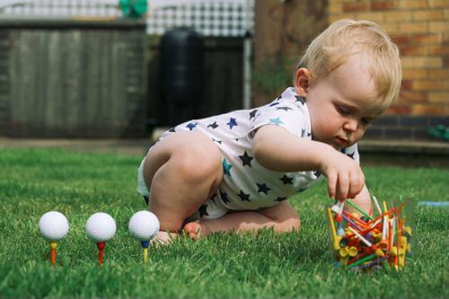 a baby playing outside in the summer