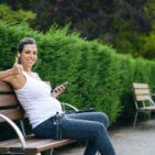 Relaxed sporty pregnant woman sitting in a park bench for resting after outdoor workout. Pregnancy successful healthy fitness lifestyle concept.