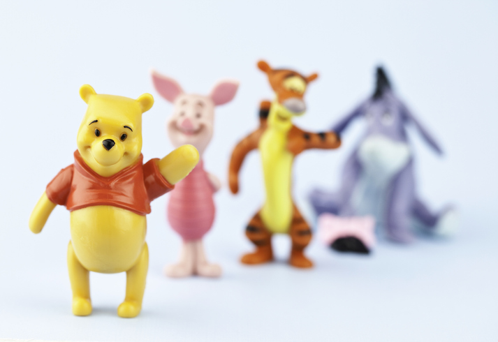 A horizontal studio shot of the fictional cartoon characters Winnie the Pooh, Piglet, Tigger and Eeyore. Here Winnie the Pooh is standing in the foreground waving and is the focal point of the image, while the other characters are defocused in the background.