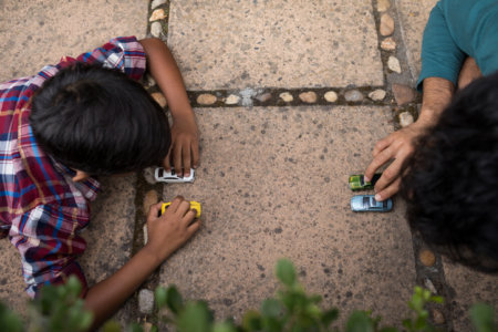 High angle view of son and father playing with toy car in yard
