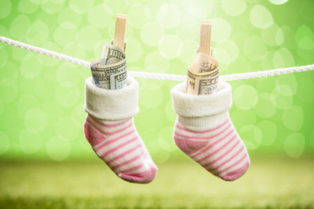Pair Of Baby Sock With Dollar Hanging On Rope Using Wooden Clip