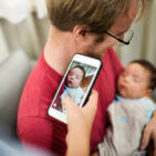 mom taking a photo of her husband and newborn baby