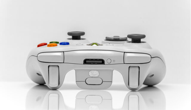 Showing a Microsoft xbox360 games console controller isolated on a white background