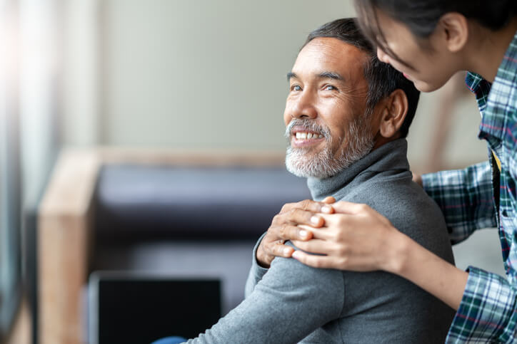 Smiling happy older asian father with stylish short beard touching daughter's hand on shoulder looking and talking together with love and care. Family relationship with bond and care concept.
